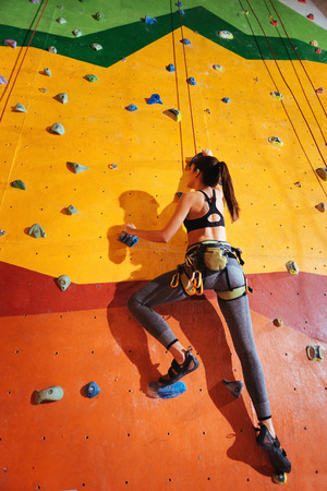 conquer: Conquer the peak. Strong young active woman climbing up the orange wall in gym while training and wearing sportswear and special equipment Stock Photo