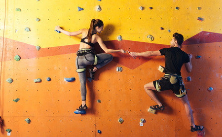 Lovely times. Joyful athletic young couple climbing up the wall together while training and holding hands in climbing gym. Stock Photo