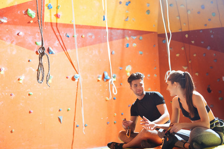 overjoyed: Common activity. Overjoyed young active couple sittiing in a climbing gym after training and climbing up the wall. Stock Photo