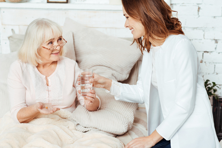 kind hearted: Kind hearted. Positive professional nurse holding glass of water and visiting sick elderly woman at home while she is lying in bed