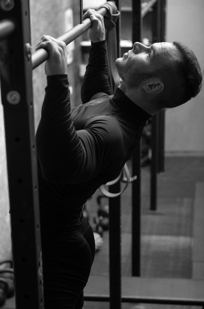 strong chin: Intensive workout. Well built strong young sportsman holding a horizontal bar and doing chin ups while working out in the gym