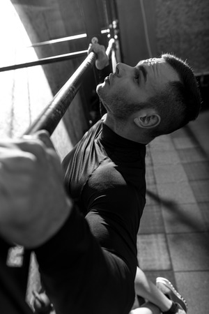 Pull up exercises. Serious well built handsome man holding a horizontal bar and doing pull ups while having an intensive workout