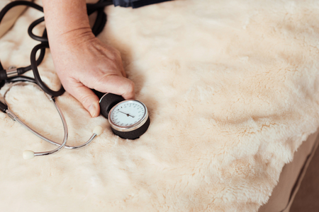 Useful device. Close up of tonometer in hands of pleasant aged woman holding tonometer while sitting in bed Stock Photo