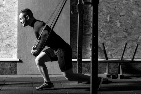 Estilo de vida saludable. Buen hombre confiado fuerte que sostiene bandas de resistencia y haciendo un ejercicio físico mientras tiene un entrenamiento de gimnasio