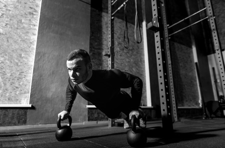 well built: Kettlebell training. Well built brutal professional sportsman holding kettlebells and doing push ups while having weight training Stock Photo