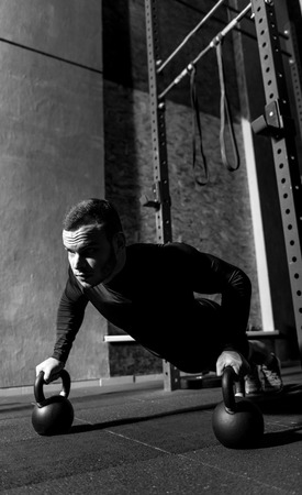 hard working: Intensive training. Hard working persistent professional weightlifter doing push ups and focusing on the task while holding kettlebells