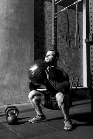 persistent: Being in a gym. Persistent confident nice man squatting and holding a medicine ball while preparing to throw it