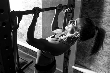 strong chin: Doing chin ups. Slim well built young woman wearing a ponytail and holding a horizontal bar while doing chin ups