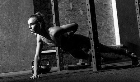 well built: Be always fit. Serious sporty well built woman holding one hand behind her back and doing push ups while keeping herself physically fit