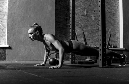 well built: Gym training. Beautiful well built young woman doing push ups and concentrating on the activity while developing her muscles Stock Photo