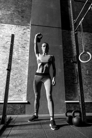 body built: Exercising with kettlebells. Well built hard working young woman holding her hand up and lifting a kettlebell while doing a physical exercise