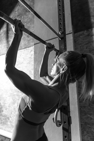 body built: Strong and beautiful. Well built athletic nice woman holding a horizontal bar and doing chin ups while developing her body Stock Photo