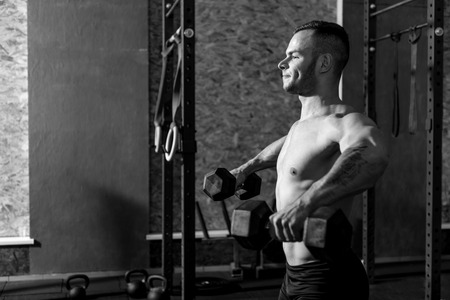 well built: Lifting weight. Muscular well built tattooed man standing in the gym and lifting dumbbells while developing his strength