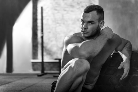 well built: Need some rest. Handsome brutal well built man sitting in front of a huge tire and looking at you while resting after an intensive workout