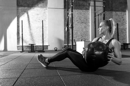 well built: Doing physical exercises. Nice slim well built woman sitting on the floor and holding a medicine ball while doing physical exercises with it