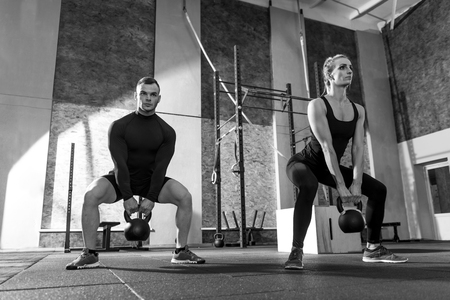 well built: Working out together. Strong good looking well built man and woman holding kettlebells and lifting them while moving synchronically Stock Photo