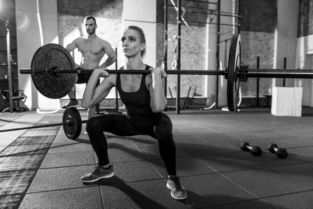 well built: Powerlifting training. Strong well built beautiful woman squatting and holding a barbell while lifting it