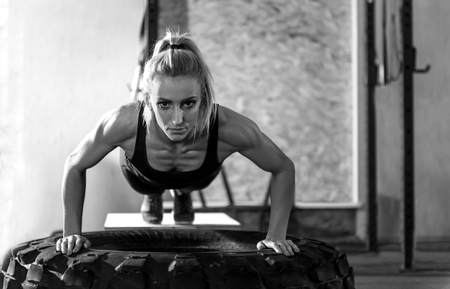 well built: Doing push ups. Muscular well built serious woman doing push ups on a giant tire and looking at you while having an intensive workout