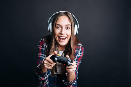 gad: Real gambler. Positive young woman smiling and playign video games while enjoying her free time