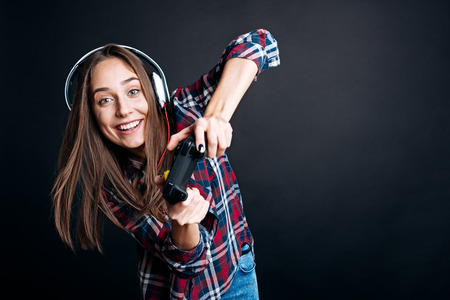 素晴らしい時間を過ごすに関与します。陽気の喜んでいる笑顔若い女性ゲーム コンソールを押し、黒背景の上に立っている間ビデオゲーム 写真素材