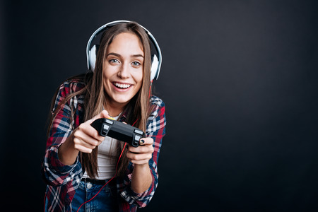 gad: My hobby. Delighted positive young woman holding game console and playing video games while standing isolated on black background