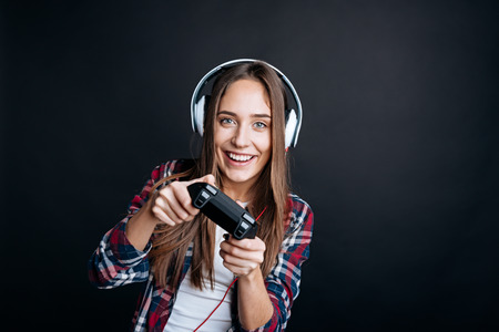 gad: Rise your mood. Delighted positive young woman playing video games and wearing headphones whle enjoying her hobby