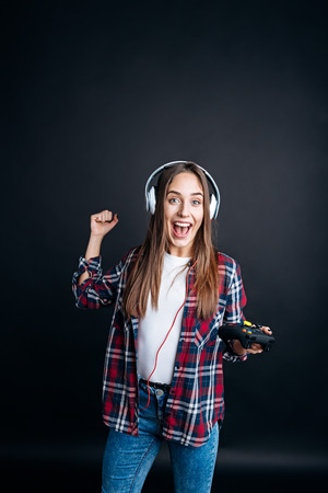 gad: I am the winner. Pleasant jubilated ypung woman smiling and playing video games while celebrating victory Stock Photo