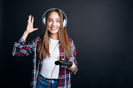 gad: Like doing it. Cheerful delighted young woman smiling and playign video games while standing isolated on black background