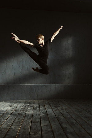 proficient: Performing split in the air. Skillful proficient young dancer performing in the dark lighted room and having a stretching session while showing his flexibility in the air
