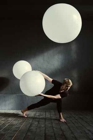 involvement: Concentrated on the result. Skillful involved masterful dancer demonstrating his talent and expressing involvement while holding white balloon in the dark lighted studio Stock Photo