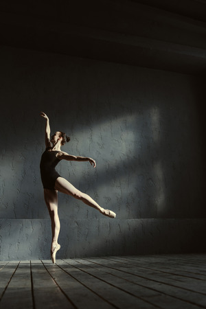 Performance of the black swan. Graceful inspired skillful ballet dancer demonstrating her abilities and expressing elegance while dancing in the black colored room and standing on the tiptoes