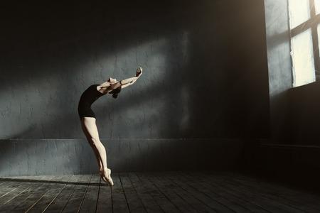 Flexibel als een kat. Elegante sierlijke ervaren balletdanser toont haar flexibiliteit en dans in de zwart gekleurde studio terwijl ze op de tenen staat en terwijl ze boven kijkt Stockfoto