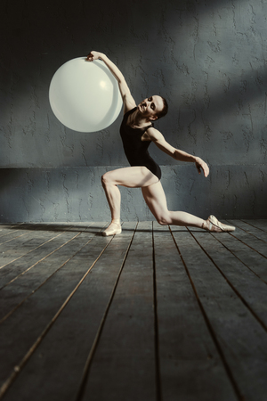 proficient: Stretching session with a balloon. Proficient skilled concentrated gymnast standing in the dark lighted studio and holding the big white balloon while performing Stock Photo