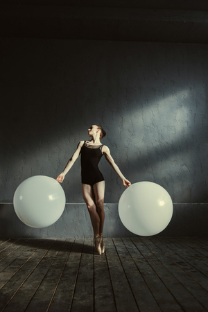 diligente: Principal ballet dancer in motion. Flexible masterful skilled ballet dancer performing isolated in the black colored room and holding two white balloons while dancing
