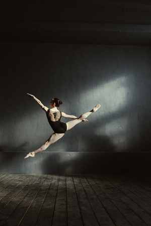 My enjoyable job. Flexible skilled young ballet dancer performing isolated in the black colored room and jumping in the twine while expressing elegance