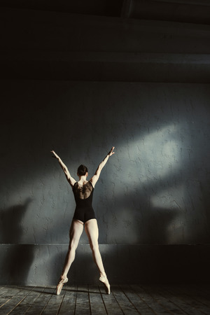 In the room full of shades. Graceful young proficient ballet dancer performing isolated in the black colored room and standing on the tiptoes while expressing elegance and femininity Stock Photo