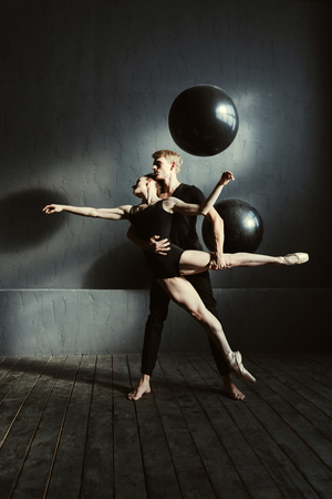 In interaction with my dance partner. Graceful skillful young ballet dancers performing together in the black colored room and expressing elegance while demonstrating their talent Stock Photo