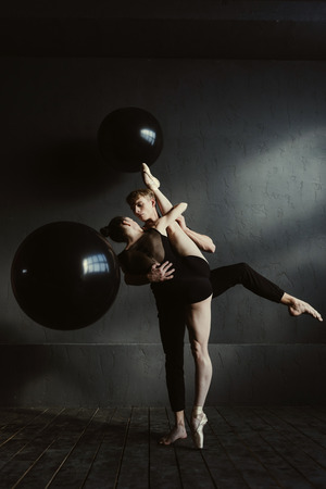 proficient: Rehearsal of two ballet dancers. Concentrated proficient flexible ballet dancers performing in the black colored studio and expressing grace and elegance while demonstrating their abilities Stock Photo