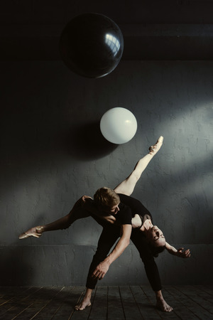 Interaction of Yin and Yang. Talented flexible masterful ballet dancers performing in the studio full of balloons and expressing grace and elegance while demonstrating their skills and flexibility