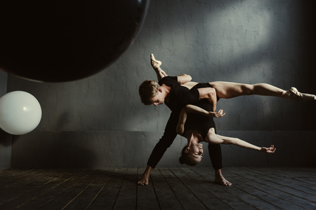 proficient: Upside down art performance. Proficient flexible young ballet dancers performing in the studio and showing their futuristic ideas while demonstrating their skills and flexibility