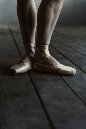 proficient: Elegant ballet dancer legs . Flexible proficient skilled ballet dancer showing her legs while standing isolated in the fourth position on the black colored floor and expressive readiness to perform