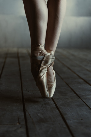 proficient: Graceful ballet dancer legs . Concentrated proficient skilled ballet dancer showing her legs while standing isolated on the tiptoes in pointes on the black colored floor and performing