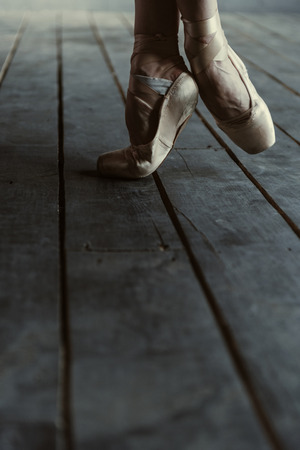 proficient: Flexibility of the ballet dancer. Experienced young proficient ballet dancer demonstrating her legs while standing isolated on the tiptoes in pointes on the black floor and stretching