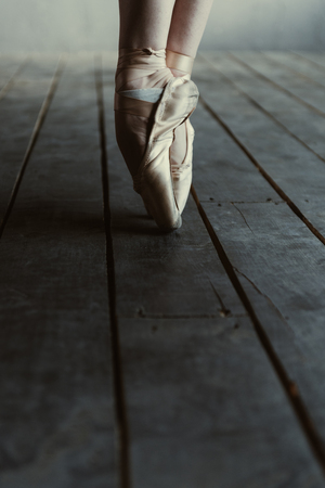 Pointes of the ballet dancer. Experienced skilled flexible ballet dancer showing her legs while standing isolated on the tiptoes in pointes on the black floor and dancing