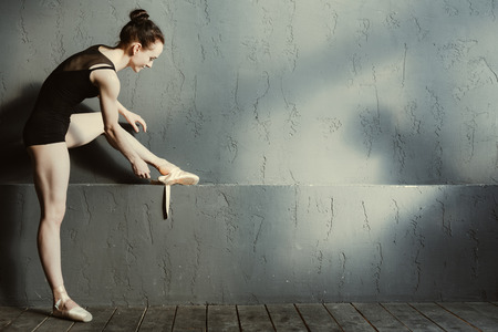 Getting ready in a positive mood. Delighted positive charming ballet dancer wearing the points while standing isolated in the black dancing saloon and getting ready for stretching Stock Photo