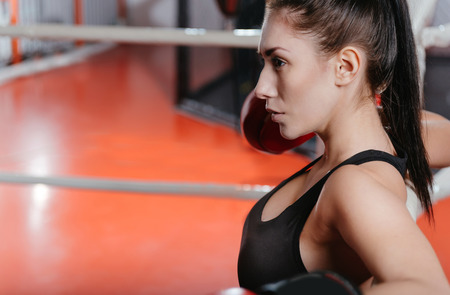 I need a minute. Exhausted athletic pretty woman taking a deep breath in the ring corner after a good sparring bout with her partner Stock Photo
