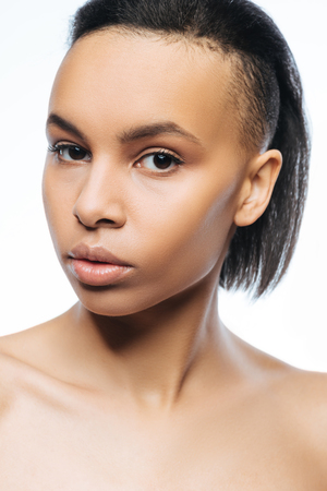 Concentrated unemotional young Negroid woman looking at the audience while standing against white background and posing