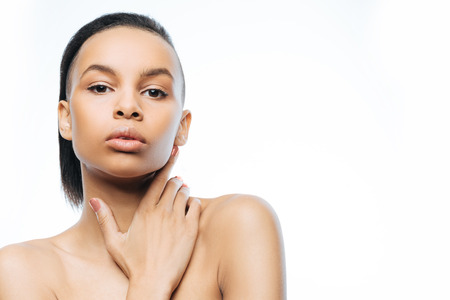 femininity: Charming graceful young Negroid woman touching her skin while standing against white background and expressing femininity Stock Photo