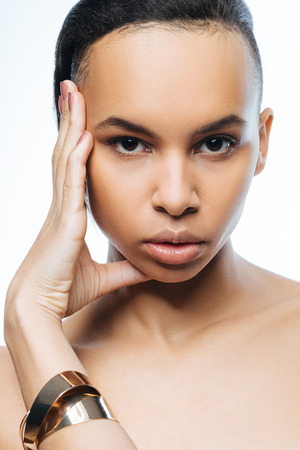 Elegant pathetic young Negroid woman touching her face while standing isolated in white background and expressing grace