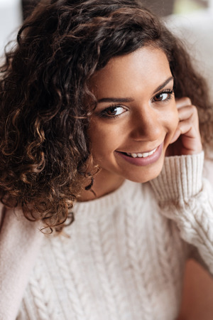 sincerely: Sharing positive atmosphere. Charming positive delighted African American woman sitting in the cafe and being covered with a blanket while smiling sincerely